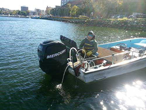 Paul Schramm on a boat on lake Mendota with the Fast Limnology Automated Measurement platform.