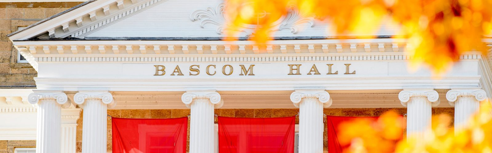 Bascom Hall and a red W banner are framed by yellow and orange autumn leaves.
