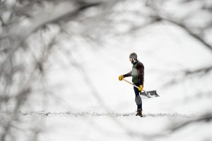 Colin Connors stands at the end of a shoveled path on a snowy lake holding a snow shovel.